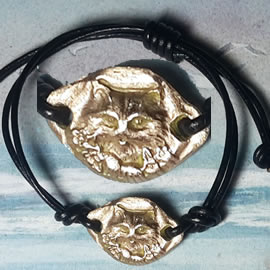 572Q--002 thin bracelet  gold bronze (or copper) long haired cat, leather strap