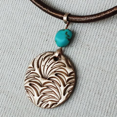 h42a3-019 Bronze Pendant round art-deco style piece with a turquoise teinted howlite
