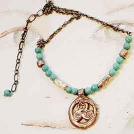 y22a-006 Necklace triskel with  bronze  and turquoise teinted howlite beads and  brass cha