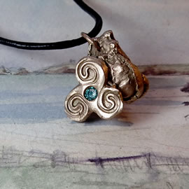 y42az-010 Bronze pendant, bronze meteorit + celtic Triskelion and an aqua blue  zirconia